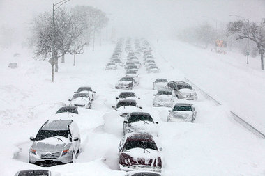 Many cars are stuck in a blizzard on the interstate.
